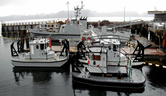 The Single Screw Log Bronc Five tractor tug moored at the service pier fueling dock at Bangor Submarine Base, Washington (WA) along with its sister tugs, the Log Bronc Seven and Eight tractor tugs. One improvement to the Log Bronc Five is the push-knees on each end of the new tugs