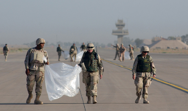 US Air Force (USAF) MASTER Sergeant (MSGT) Kenny Denmore (left), SENIOR MASTER Sergeant (SMSGT) Debra Huntley (center) and SMSGT Annie Reid, all First Sergeants deployed to Balad Air Base (AB), Iraq (IRQ)'s 332 Air Expeditionary Wing (AEW) participate in a Foreign Object or Debris (FOD) walk on the runway areas before deployed aircraft land in support of Operation IRAQI FREEDOM