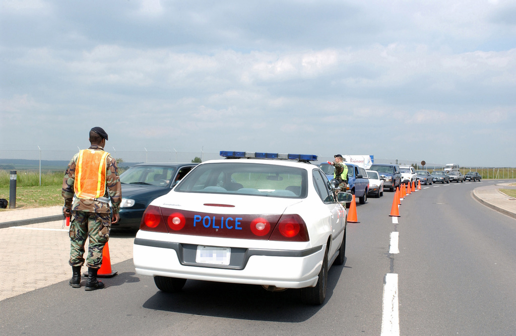 """A long line of cars stop and have their cars checked for seatbelt violations in support of the US Air Force (USAF) 52nd Fighter Wing (FW), Spangdahlem Air Base (AB), Germany (DEU) biannual """"Click it or Ticket"""" campaign"""