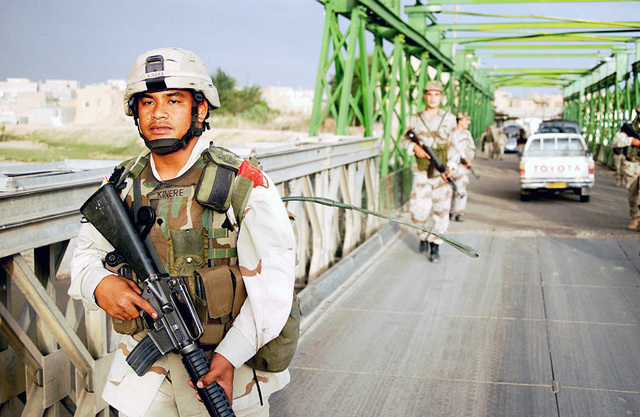 Just before dusk, US Army (USA) SPECIALIST Fourth Class (SPC) Kinere, C Battery 2nd Battalion 11th Field Artillery Regiment 25th Infantry Division (ID), Schofield Barracks, Hawaii (HI), crosses a bridge with soldiers of the Iraqi Civil Defense Corp (ICDC), during a joint foot patrol of Altun Kapri, Iraq, for the purposes of training the ICDC to take over the area during Operation IRAQI FREEDOM