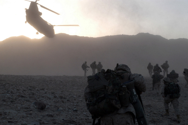 US Marine Corps (USMC) Marines from 3rd Battalion, 6th Marines, move to their security positions after offloading from a US Army (USA) CH-47 Chinook helicopter at Wusbin Valley, Afghanistan, during Operation ENDURING FREEDOM