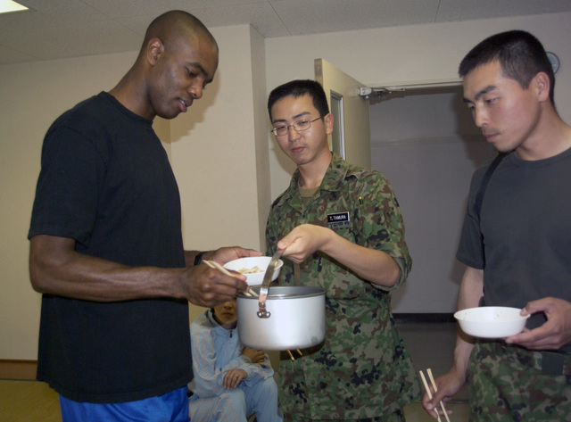 "US Marine Corps (USMC) STAFF Sergeant (SSGT) Robert Thomas (left) Legal Services CHIEF, from Marine Corps Air Station (MCAS) Iwakuni, Japan, eats ""Udon"" noodles with Japanese Maritime Self Defense Force (JMSDF) Sailors, during his visit aboard Camp Otsu, Japan"