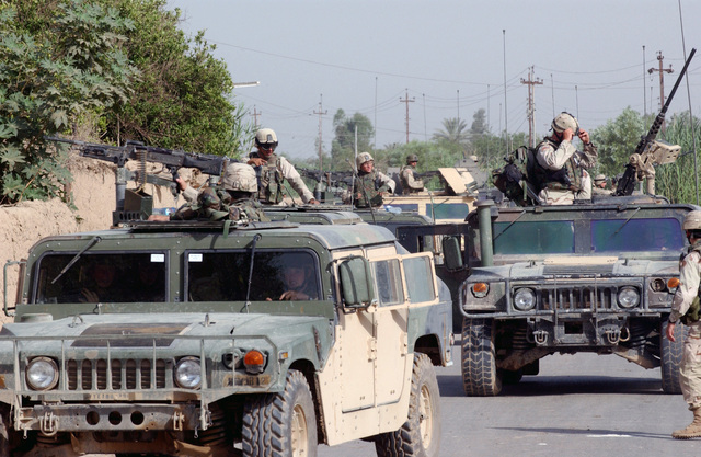 A convoy of US Army (USA) Soldiers from HHC 1-77th Armor Battalion, Schweinfurt, Germany (DEU) prepare a convoy in a small Iraqi village following local Operation Rocket Man in support of Operation IRAQI FREEDOM. USA Scouts are armed with 5.56 mm M16A2 Automatic Rifles and travel in High-Mobility Multipurpose Wheeled Vehicles (HMMWV)
