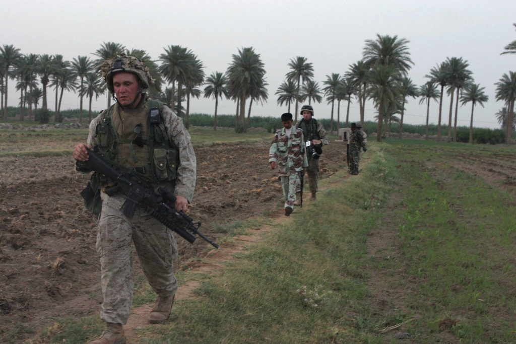 Iraqi Civil Defense Corps (ICDC) soldiers join US Marine Corps (USMC) Marines from 1ST Platoon (PLT), 1ST Battalion (BN), 5th Marines (MAR) (1/5), Bravo Company (B Co), 1ST Marine Division (MAR DIV), in searching farmland in eastern Al Shahabi, Iraq, during Operation IRAQI FREEDOM. The Marine is armed with a 5.56 mm M16A2 rifle with an M203 40 mm grenade launcher. The 1ST MAR DIV is engaged in Security and Stabilization Operations (SASO) in the area