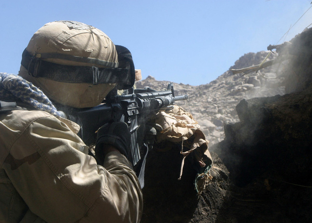 A US Marine Corps (USMC) rifleman with Battalion Landing Team (BLT), 1ST Battalion, 6th Marines and the ground combat element of the 22nd Marine Expeditionary Unit (MEU), sprays Colt 5.56 mm M16A2 Assault Rifle rounds toward Taliban positions on a mountain near the village of Siah Chub Kalay, Afghanistan (AFG) during Operation ASBURY PARK and in support of Operation ENDURING FREEDOM