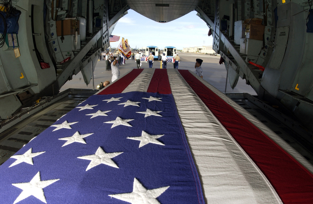During a commemorative ceremony at Hickam Air Force Base (AFB) Hangar 35, inside a US Air Force (USAF) C-17A Globemaster III, members of a joint honor guard prepare to carry the remains believed to be of unaccounted-for Americans, recovered in Vietnam and Papua New Guinea. The remains will be taken to the Joint POW/MIA Accounting Command's Central Identification Laboratory (JPAC CIL) where they will attempt to positively identify the remains so they can be returned to their families
