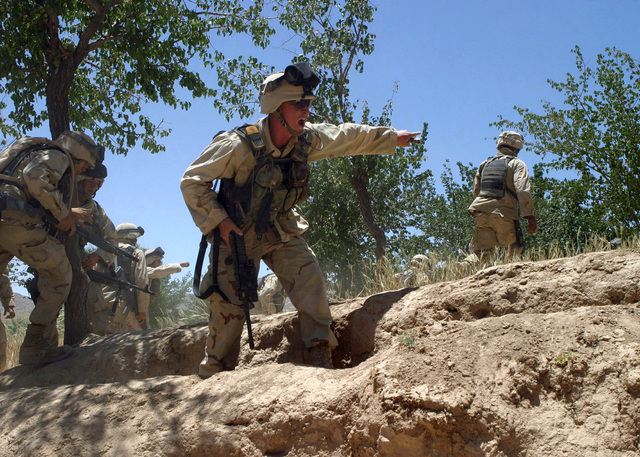 US Marine Corps (USMC) Sergeant (SGT) Ryan West (foreground), Squad Leader assigned to Battalion Landing Team (BLT), 1ST Battalion, 6th Marines, 22nd Marine Expeditionary Unit (MEU), Special Operations Capable (SOC), yells for his Marines to take cover from intense enemy sniper fire during a firefight with Taliban insurgents on a mountain range near the village of Siah Chub Kalay, Afghanistan, during Operation Asbury Park.  During eight days of intense fighting more than 80 Taliban fighters were killed while eight Marines were wounded in the most intense clashes during the MEU's deployment in support of Operation ENDURING FREEDOM