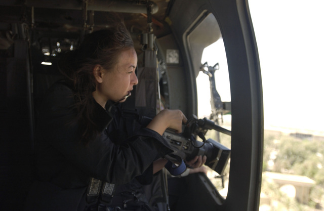 A Singapore reporter prepares to take video footage of Baghdad while flying in a UH-60 Black Hawk (Blackhawk) helicopter during Operation IRAQI FREEDOM