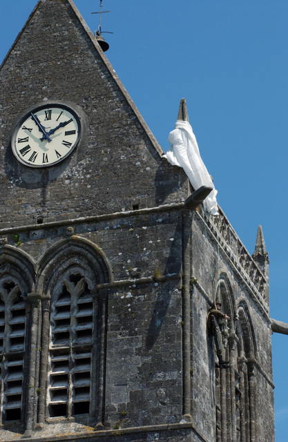 The church of St. Mere Eglise, France, still has a mannequin hanging off its steeple, commemorating US Army (USA) Private (PVT) John M. Steele, paratrooper, 505th Parachute Infantry Regiment (PIR), 82nd Airborne Division (ABN DIV), whose parachute was caught on the church during the airdrops very early on June 6th 1944