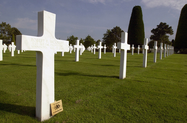 The Latin Cross marker of US Army (USA) First Lieutenant (1LT) Robert F. Bickhart, from Minnesota, 165th Signal PHOTO Company, killed in action (KIA) August 25, 1944, during World War II (WWII) along with more than 9,000 Americans killed in the Normandy, France, region. They were laid to rest in the American Cemetery in the village of Colleville-sur-Mer overlooking Omaha Beach. Among those buried are more than 300 unknown Soldiers