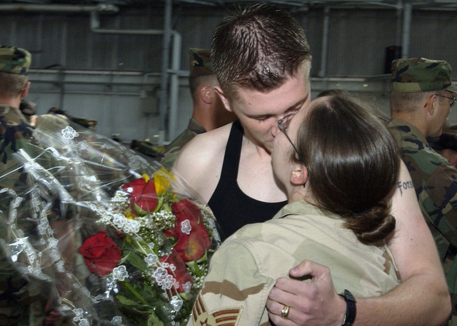 US Air Force (USAF) AIRMAN First Class (A1C) Derek Crisman greets his wife USAF SENIOR AIRMAN (SRA) Renee Crisman with flowers and a kiss as the 31st Fighter Wing (FW) welcomes home members of the 603rd Air Control Squadron (ACS) in Hangar 1 at Aviano Air Base, Italy (ITA). USAF SRA Crisman and fellow members just returned from a seven-month deployment at Balad Air Base (AB), Iraq (IRQ), in support of Operation IRAQI FREEDOM