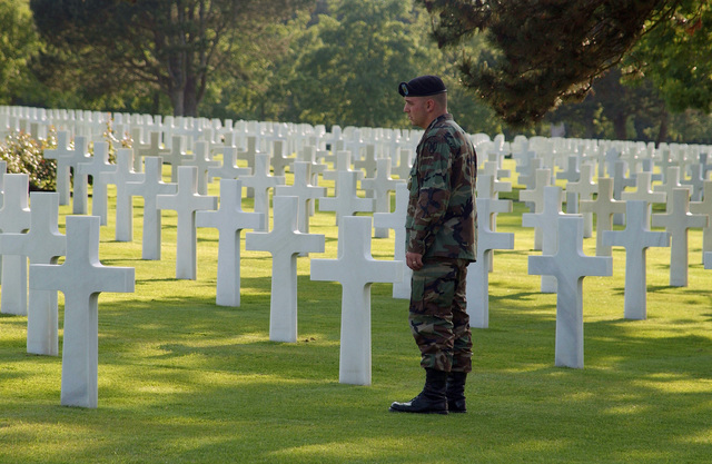 US Army (USA) SPECIALIST Fourth Class (SPC) Ryan Hildebran, 529th Military Police Company (MP CO), Heidelberg, Germany (DEU), walks through the American Cemetery during the 60th Anniversary of D-Day viewing the Latin Cross markers of American servicemen killed during World War II (WWII). The cemetery is in the village of Colleville-sur-Mer, France (FRA), overlooking Omaha Beach