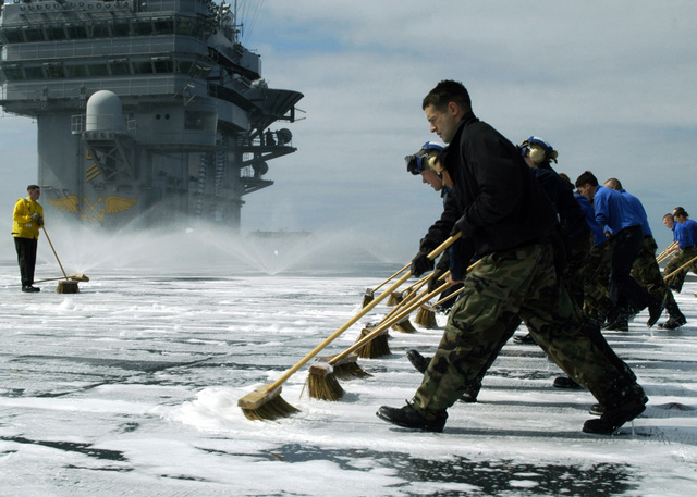 US Navy (USN) Sailors assigned to Air Department Divisions V-1 and V-3 scrub down the flight deck of the USN Nimitz Class Aircraft Carrier, USS ABRAHAM LINCOLN (CVN 72), during a countermeasures system washdown. The LINCOLN is currently underway in the Pacific Ocean, conducting local operations in preparation for deployment