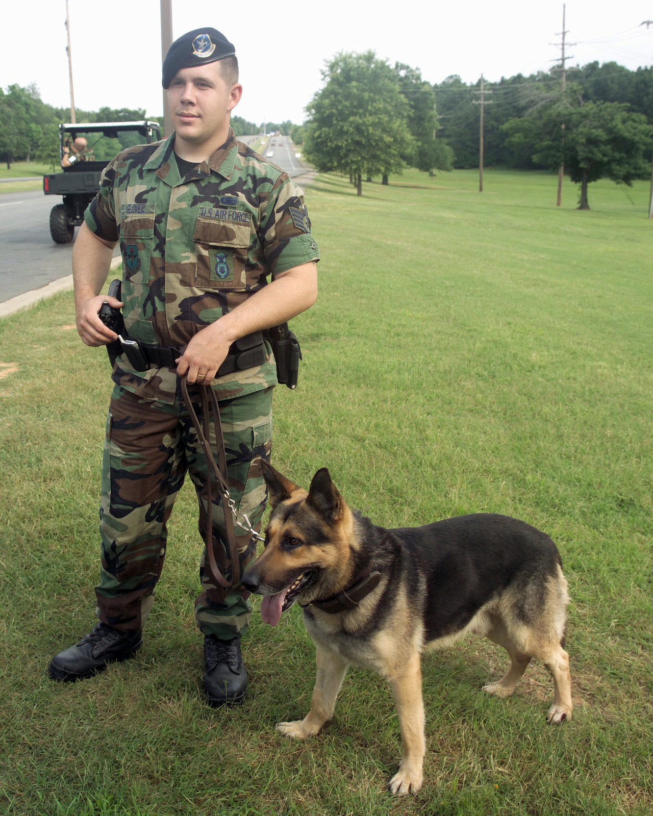 At the front gate of Little Rock Air Force Base (AFB), US Air Force (USAF) STAFF Sergeant (SSGT) Troy Glover, 314th Security Forces Squadron (SFS), waits, with Benny his K-9 Partner, to check cars for unauthorized items during the 2004 Heroes of the Heartland Air Show