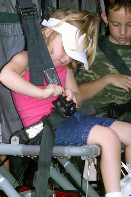 Abby Holtfort, daughter of US Air Force (USAF) Technical Sergeant (TSGT) William Falker, Non-Commissioned Officer (NCOIC) of Commander Support STAFF, 314th Medical Group (MDG), tries to buckle up herself aboard a helicopter at the 2004 Heroes of the Heartland Air show at Little Rock Air Force Base (AFB), Arkansas (AR)
