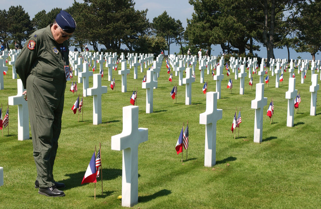 D-Day veteran US Air Force (USAF) Lieutenant Colonel (LTC) (Ret) Wayne Chase, 15th Troop Carrier Squadron (TCS), pauses to reflect at the grave of an unknown Soldier in Normandy American Cemetery OMAHA Beach. France (FRA), after a D-Day ceremony. This year marks the 60th Anniversary of the Normandy invasion during World War II (WWII)