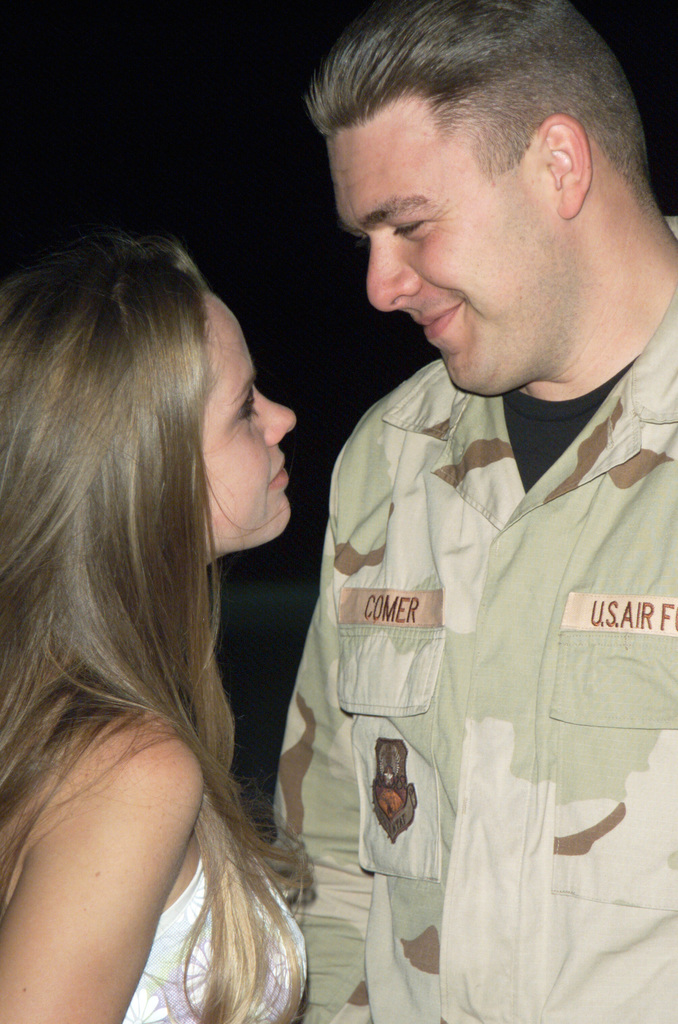 US Air Force (USAF) STAFF Sergeant (SSGT) Chad Comer, 43rd Expeditionary Communications Squadron (CS), Davis-Monthan Air Force Base (AFB), Arizona (AZ), takes a moment greet his wife Kristi after greeting his sons Logan and Tristan. The family was separated for three and a half months as SSGT Comer deployed for Operation IRAQI FREEDOM