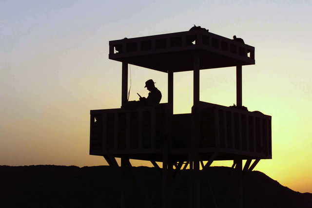 From a watchtower US Marine Corps (USMC) Lance Corporal (LCPL) Rueben E. Rodriguez, Alpha Battery (A BTY), 1ST Battalion, 11th Marine Regiments (11th Marines) (1/11), 1ST Marine Division (MAR DIV), stands watch over the living area aboard Camp Fallujah, Iraq (IRQ). The 1ST MAR DIV, in support of Operation IRAQI FREEDOM, is engaged in Security and Stabilization Operations (SASO) in Iraqs Al Anbar province