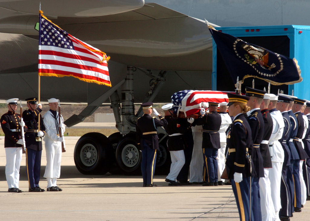 A US Military Multi-Service Ceremonial Honor Guard places flag draped coffin of Former US President Ronald Reagan aboard US Air Force VC-25 Special Airlift Mission (SAM) 2800, a Boeing 747 aircraft, at Point Mugu Naval Base, California. The Presidents body will be flown to Washington, District of Columbia (DC), where it will lie in state in the Capitol Rotunda, to be followed by a state funeral conducted at the Washington National Cathedral