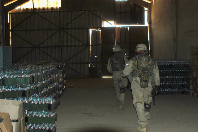 US Army (USA) Sergeant (SGT) Derick D. Fisher, and Private First Class (PFC) Rosario Leotta III, both assigned to Troop D, 4th Cavalry, 1ST Infantry Division, Brigade Combat Team 1 (BCT-1), search the interior of a building at the glass factory in Ar Ramadi, Iraq. USA Soldiers assigned to the 1ST Infantry Division are attached with the US Marine Corps (USMC) 1ST Marine Division, and are engaged in Security and Stabilization Operations (SASO) in the Al Anbar Province of Iraq, in support of Operation IRAQI FREEDOM