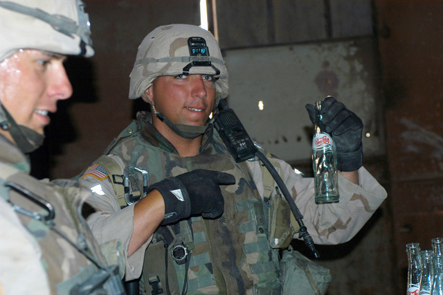 US Army (USA) Sergeant (SGT) Derick D. Fisher, assigned to Troop D, 4th Cavalry, 1ST Infantry Division, Brigade Combat Team 1 (BCT-1), holds up an empty Iraqi Pepsi Cola bottle, as his Unit searches the interior of a building at the glass factory in Ar Ramadi, Iraq. USA Soldiers assigned to the 1ST Infantry Division are attached with the US Marine Corps (USMC) 1ST Marine Division, and are engaged in Security and Stabilization Operations (SASO) in the Al Anbar Province of Iraq, in support of Operation IRAQI FREEDOM