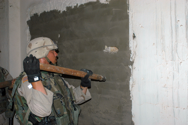 US Army (USA) Sergeant (SGT) Derick D. Fisher, assigned to Troop D, 4th Cavalry, 1ST Infantry Division, Brigade Combat Team 1 (BCT-1), gains access to a sealed compartment, as he conducts a search for weapons inside the glass factory in Ar Ramadi, Iraq. USA Soldiers assigned to the 1ST Infantry Division are attached with the US Marine Corps (USMC) 1ST Marine Division, and are engaged in Security and Stabilization Operations (SASO) in the Al Anbar Province of Iraq, in support of Operation IRAQI FREEDOM