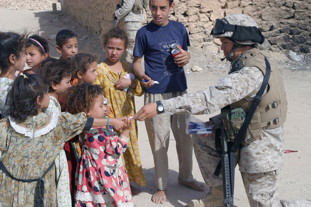 US Marine Corps (USMC) Corporal (CPL) Grand Lee, Civil Affairs (CA) Section, Weapons Company, 2nd Battalion (BN), 7th Marine Regiment, 1ST Marine Division (MAR DIV), hands out writing pens to local children in Hit, Iraq, during a Security and Stabilization Operation (SASO) in Al Anbar Province in support of Operation IRAQI FREEDOM