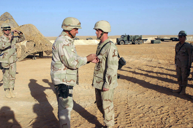 At Ar Ar, Iraq (IRQ), US Navy (USN) Rear Admiral (RADM) Charles Kubic, Commander of First Naval Construction Division, presents a Purple Heart medal to a PETTY Officer Third Class (PO3) Mangrum of Sea Bees Detachment 74, for a wound he received during a firefight in Fallujah, Iraq, in support of Operation IRAQI FREEDOM