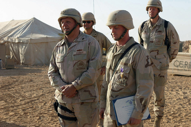 At Ar Ar, Iraq (IRQ), US Navy (USN) Rear Admiral (RADM) Charles Kubic (left), Commander of First Naval Construction Division, presents a Purple Heart medal to a PETTY Officer Third Class (PO3) Mangrum of Sea Bees Detachment 74, for a wound he received during a firefight in Fallujah, Iraq, in support of Operation IRAQI FREEDOM