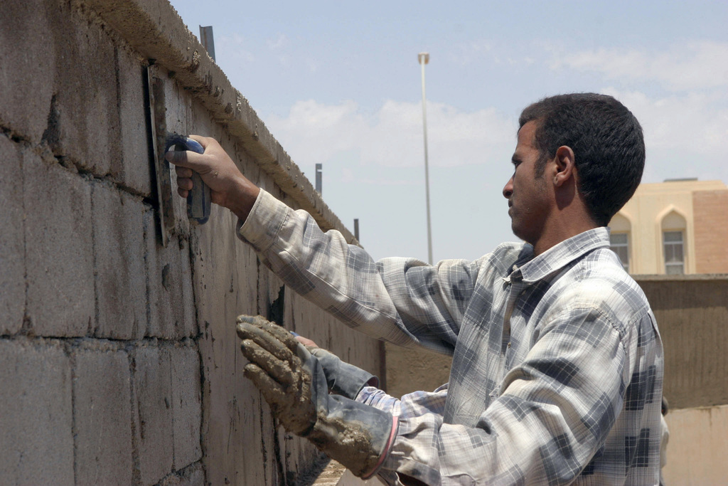 A local Iraqi civilian uses a hand trowel to smooth out the