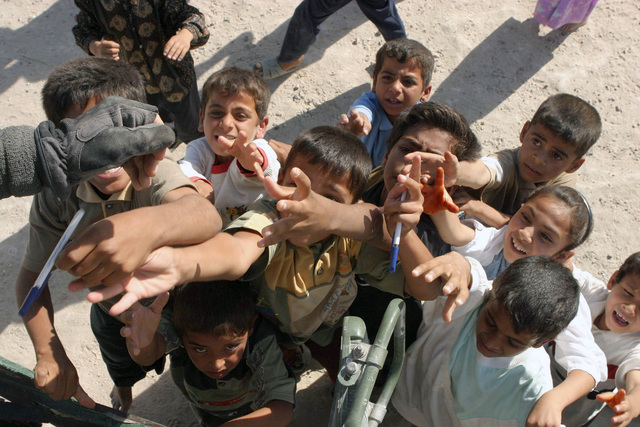 Iraqi children reach up for pens and pencils handed out by a US Marine Corps (USMC) Marine with Bravo Company, 1ST Battalion (BN), 5th Marines (MAR), 1ST Marine Division (MAR DIV), in Al Shahabi, Iraq, during Operation IRAQI FREEDOM. The 1ST MAR DIV is engaged in Security and Stabilization Operations (SASO) in the area