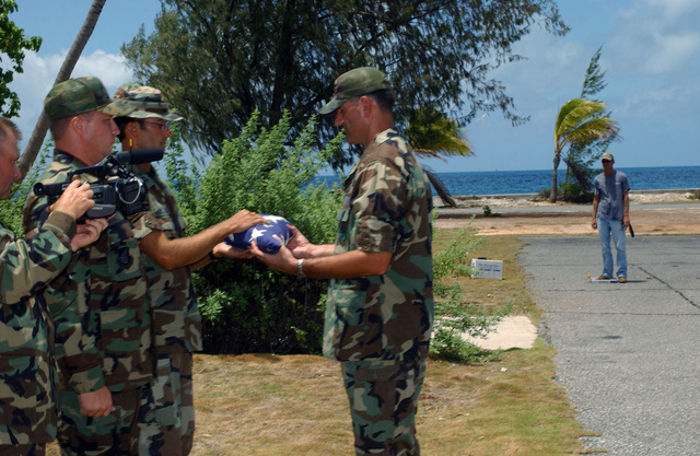 US Air Force (USAF) Captain (CPT) Eric Sassi gives USAF Colonel (COL) John Medeiros the folded American flag of Johnston Atoll marking the end of a military and civilian presence on the small South Pacific island