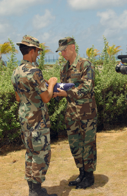 US Air Force (USAF) SENIOR MASTER Sergeant (SMSGT) Dale Brocious (right) gives USAF Captain (CPT) Eric Sassi the American Flag during the flag folding ceremony, marking the end of USAF CPT Sassi's command, and the decommissioning of Johnston Atoll. When they depart it will leave the small South Pacific island, uninhabited by humans