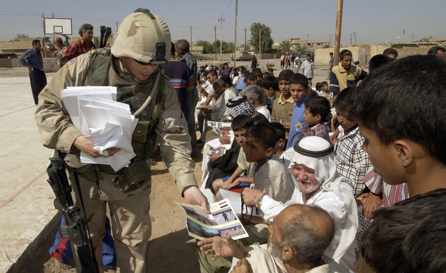 US Army (USA) Captain (CPT) Jason Colbert, 1ST Battalion, 7th Cavalry Regiment (1-7 CAV), 5th Brigade Combat Team (BCT), 1ST Cavalry Division (CD), distributes programs before several ground-breaking ceremonies take place in the Al Rasheed district of Baghdad, Iraq (IRQ), during Operation IRAQI FREEDOM