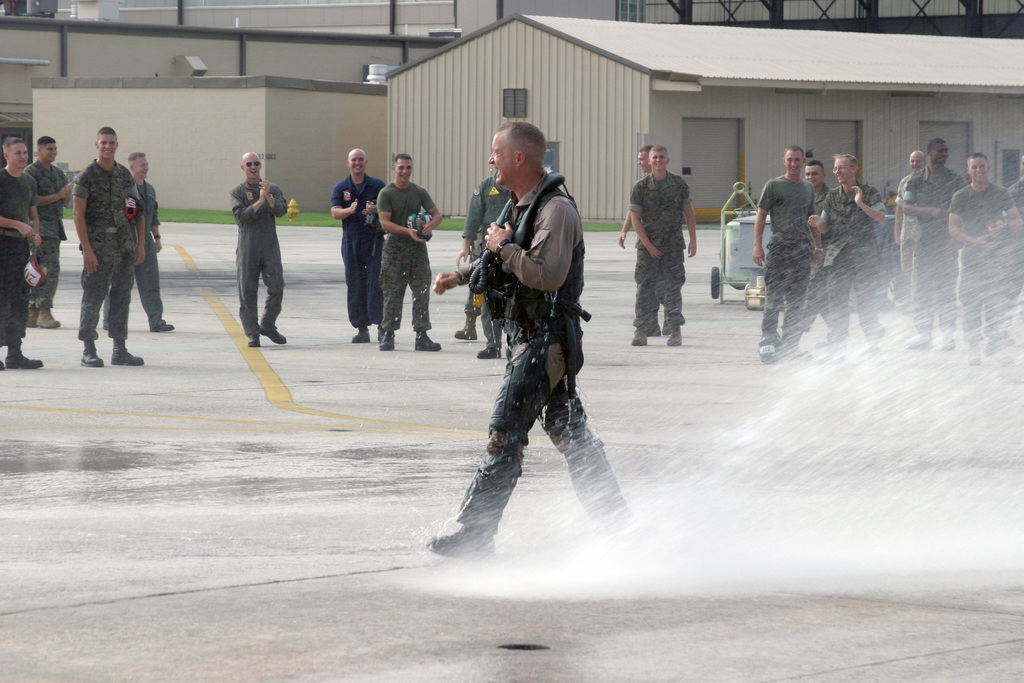 US Marine Corps (USMC) Colonel (COL) David H. Peeler, Commanding Officer, Marine Aircraft Group Three One (MAG-31), allows the Marines to have their fun soaking him down with spray of a fire hose, while receiving the Fini Flight traditional honors after completing his last flight aboard Marine Corps Air Station (MCAS) Beaufort, South Carolina (SC)