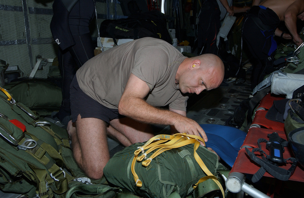 US Air Force (USAF) Pararescueman from the 38th Rescue Squadron (RS), Moody Air Force Base (AFB) Georgia (GA), prepares his gear as the Pararescue Team is 350 miles north east of St. Maarten to provide medical support to a injured Chinese fisherman aboard his boat the Yuh Pao