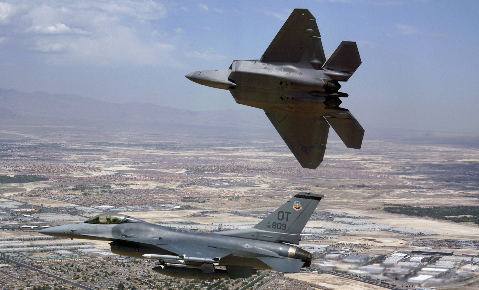 A US Air Force (USAF) F/A-22 Raptor, flown by USAF Major (MAJ) David Thole, 422nd Test and Evaluation Squadron (TES), Nellis Air Force Base (AFB), Nevada (NV), breaks away after completing a training mission with a USAF F-16 Fighting Falcon fighter, flown by MAJ Alex Grynkewich, 53rd Test and Evaluation Group (TEG), Nellis AFB, NV