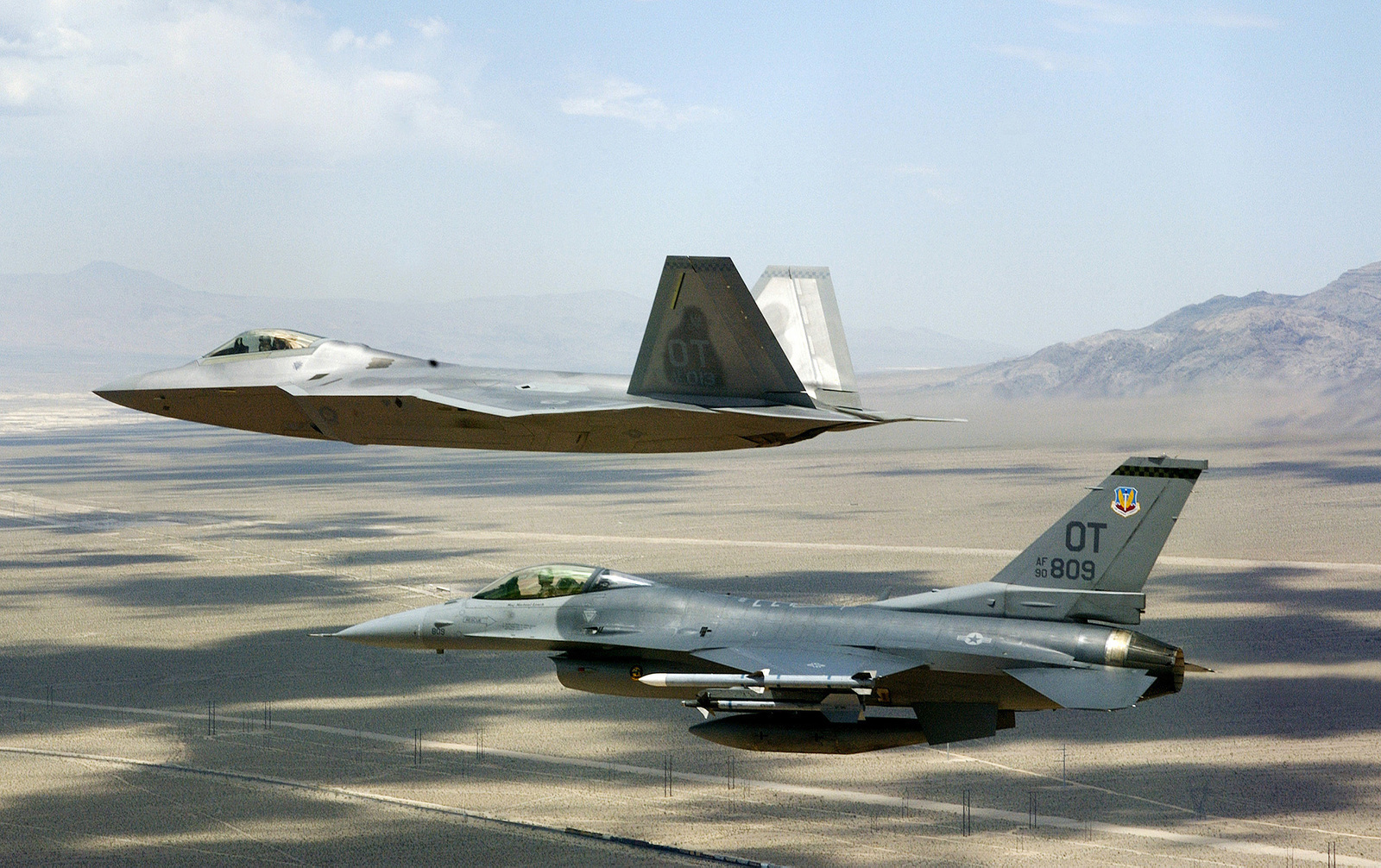 A US Air Force (USAF) F/A-22 Raptor flown by USAF Major (MAJ) David Thole, 422nd Test and Evaluation Squadron (TES), Nellis Air Force Base (AFB), Nevada (NV), flies fingertip formation on a training mission alongside an USAF F-16 Fighting Falcon, flown by USAF MAJ Alex Grynkewich, 53rd Test and Evaluation Group (TEG), Nellis AFB, NV