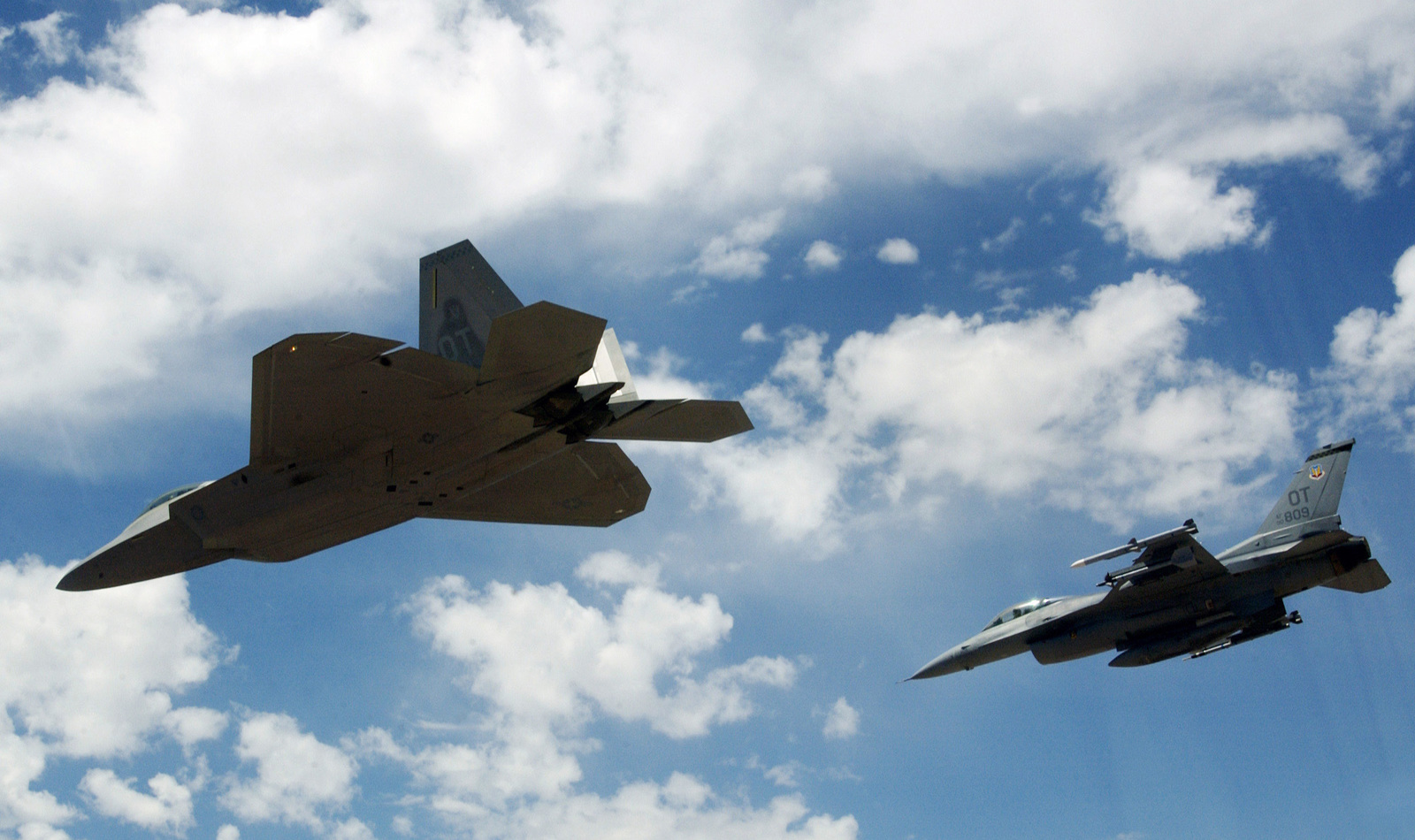 A US Air Force (USAF) F/A-22 Raptor, flown by USAF Major (MAJ) David Thole, 422nd Test and Evaluation Squadron (TES), Nellis Air Force Base (AFB), Nevada (NV), flies in formation on a training mission alongside a USAF F-16 Fighting Falcon fighter, flown by MAJ Alex Grynkewich, 53rd Test and Evaluation Group (TEG), Nellis AFB, NV