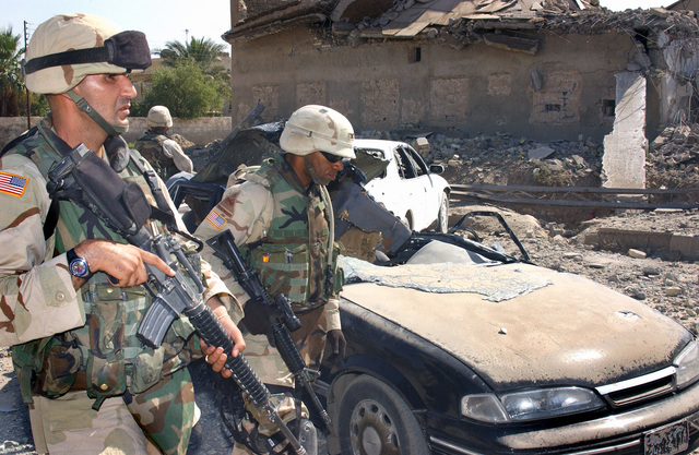 US Army (USA) Colonel (COL) Dana J. H. Pittard (right), Commander, 3rd Brigade Combat Team, 1ST Infantry Division, inspects buildings and vehicles bombed by Coalition Forces during Operation IRAQI FREEDOM. The rebel forces attempted to build stronghold points in the local urban area. The struggle during the insurgent uprising left a death toll of approximately 15 Iraqi police officers, 2 US Soldiers, and more than 30 rebels