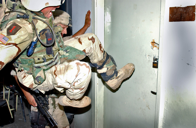 US Army (USA) Soldiers from the 3rd Brigade Combat Team, 1ST Infantry Division (ID), secure one of the stronghold buildings, in the city of Ba'qubah, Iraq, by going from room to room during Operation IRAQI FREEDOM. The struggle during the insurgent uprising left a death toll of approximately 15 Iraqi police officers, 2 US Soldiers, and more than 30 rebels