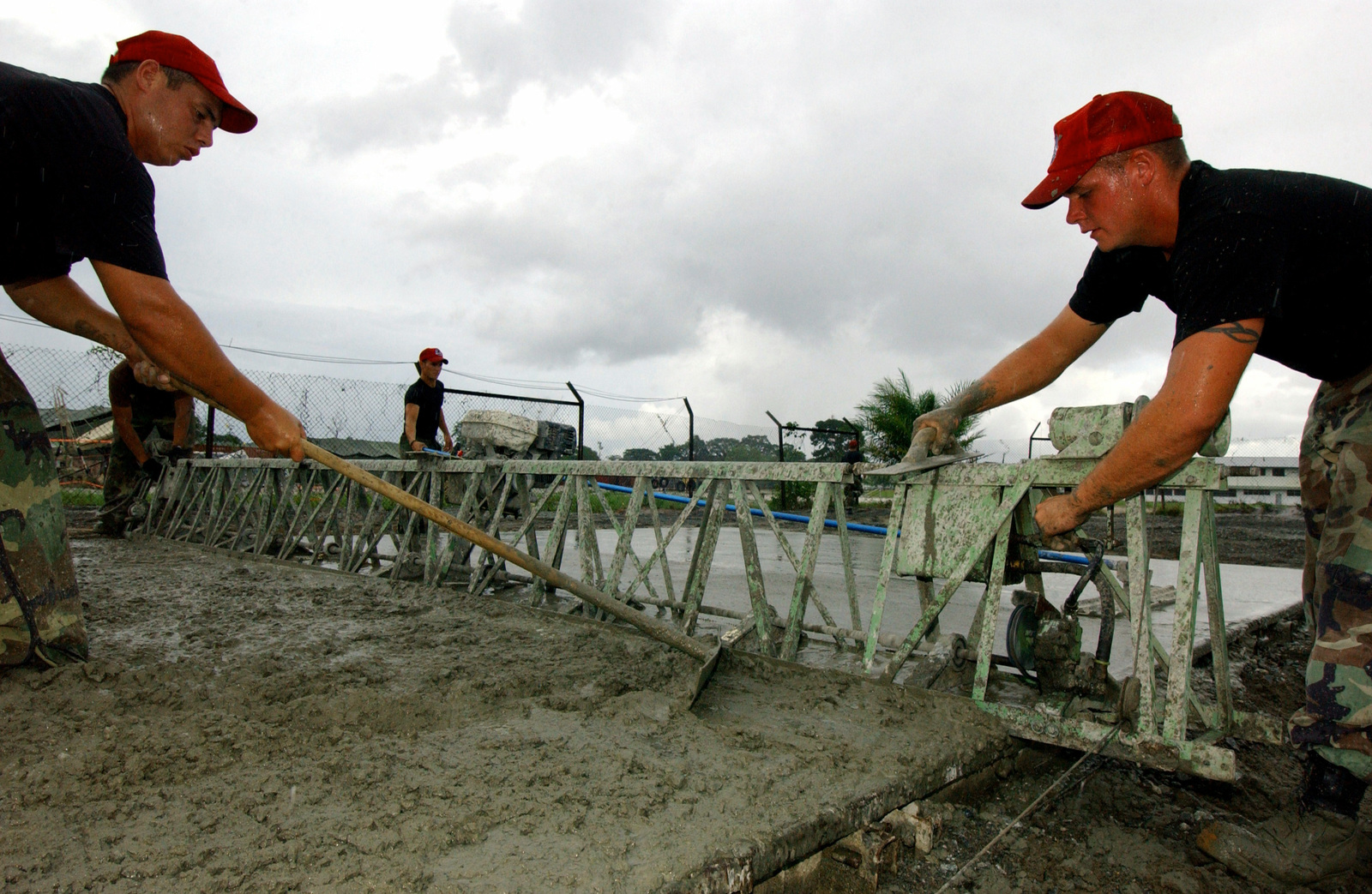 US Air Force (USAF) SENIOR AIRMAN (SRA) Miguel Gastelum from the 820th Red Horse Squadron (RHS), spreads concrete as AIRMAN 1ST Class (A1C) Garett Jentry releases the tension on a skew as it passes over the frame in support of Exercise New Horizons 2004-Guyana (GUY). The New Horizons 2004 Guyana mission is a joint service training exercise held in Guyana, South America and co-sponsored by both the US Southern Command (SOUTHCOM) and the Guyana (GUY) Defense Force (GDF)