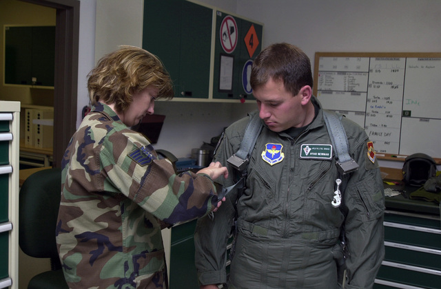 US Air Force (USAF) Technical Sergeant (TSGT) Michelle Bell, Non Commissioned Officer In Charge (NCOIC) of Life Support for the 308th Fighter Squadron (FS), 56th Fighter Wing (FW), Luke Air Force Base (AFB), Arizona (AZ), fits NASCAR driver and Winston Cup Champion Ryan Newman with a G-Suit. Ryan Newman received an incentive flight