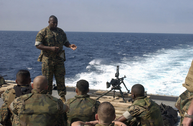 Onboard the US Navy (USN) Dock Landing Ship, USS HARPERS FERRY (LSD 49), US Marine Corps (USMC) GUNNERY Sergeant (GYSGT) Eric T. Baker, a Weapons Handler assigned to Headquarters and Service Detachment, 3rd Force Service Support Group (FSSG), briefs Marines and Sailors on the operation of the 7.62mm M240G machine gun while enroute to Vladivostok, Russia. Marines and Sailors of the 3rd Marine Division and the 3rd Force Service Support Group (FSSG) will be representing the US Military during the Annual Vladivostok Port Visit, in an effort to maintain and enhance constructive relations between the US and Russian Military Forces