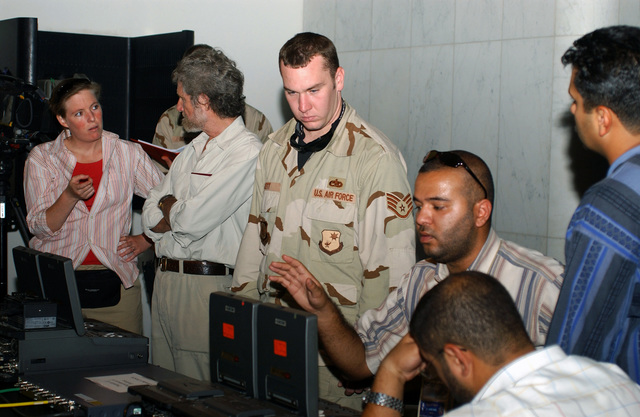 US Air Force (USAF) STAFF Sergeant (SSGT), Nate Lett (center), from the 1ST Combat Camera Squadron (CCS), at Charleston Air Force Base (AFB), South Carolina (SC), helps Jos Mason from CBS News (left) and Mohammed Al Shamene from Aljazeerd News, with the video tape editing equipment for the courtroom were former Iraqi President Saddam Hussein is being tried for war crimes, at the Baghdad, Convention Center, Iraq (IRQ)