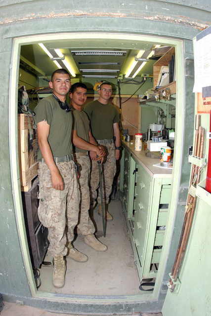 US Marine Corps (USMC) Corporal (CPL) Justin Ramirez (left), USMC Lance Corporal (LCPL) jacob Gonzales and USMC Sergeant (SGT) James Wilson, Alpha Company (A CO), 3rd Assault Amphibious Battalion (AAB), 1ST Marine Division (MARDIV), pose for a picture inside a communications vehicle at Camp Fellujah, Al Anbar Province, Iraq (IRQ).  The 1ST MARDIV is engaged in Security and Stabilization Operations (SASO) in the area in support of Operation IRAQI FREEDOM