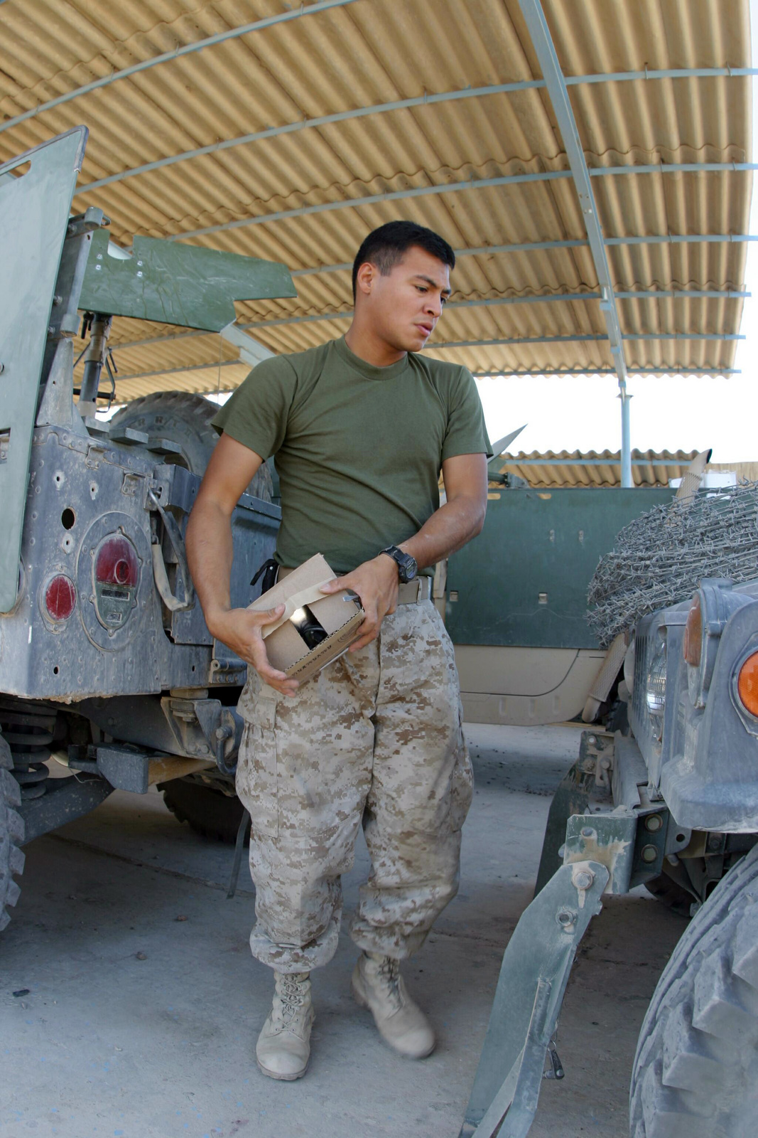 US Marine corps (USMC) Marine, pictured between two M1114 Up-Armored High Mobility Multipurposed Wheeled Vehicles (HMMWV), from Alpha Company (A CO), 3rd Assault Amphibious Battalion (AAB), 1ST Marine Division (MARDIV), performs monthly vehicle maintenance at Camp Fellujah, Iraq (IRQ). The 1ST MARDIV, in support of Operation IRAQI FREEDOM, is engaged in Security and Stabilization Operations (SASO) in the Al Anbar Province of Iraq