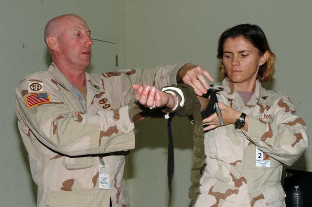 STAFF SGT. Thomas J. Brennan, Multi-National Corps - Iraq Surgeons's Cell, Camp Victory, Iraq, applies the Special Operations Forces Tactical Tourniquet to the arm of SGT. Sherrie M. Knight, MNCI Surgeon's Cell, during a class July 4, 2005 at Camp Victory.  (U.S. Army photo by SPC. Jeremy D. Crisp.)