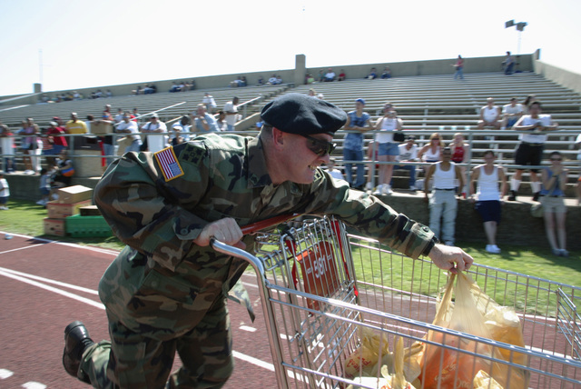 US Army (USA) Sergeant (SGT) Robert L. Schultz, 124th Signal Battalion (BN), 4th Infantry Division (ID), pushes a shopping cart as he races to the finish line in the HEB Grocery Cart Shopping Spree, one of the many contestant activities taking place at Freedom Fest 2004, the Independence Day celebration at Hood Stadium, Fort Hood, Texas (TX). Freedom Fest 2004 is sponsored by the Fort Hood Family Readiness Group to raise funds for the homecoming ceremonies for the US Army (USA) 1ST Cavalry Division Soldiers when their tour in Iraq supporting Operation IRAQI FREEDOM is finished