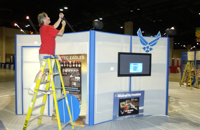 Ed Lambert, project manager, Blair Inc., Springfield, Virginia (VA), installs lighting for an US Air Force (USAF) exhibit before the start of the League of United Latin American Citizens (LULAC) at the 75th Annual National Convention and Exposition at the Henry B. Gonzalez Convention Center in San Antonio, Texas (TX)